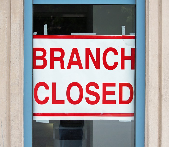 A branch closed sign in a window.