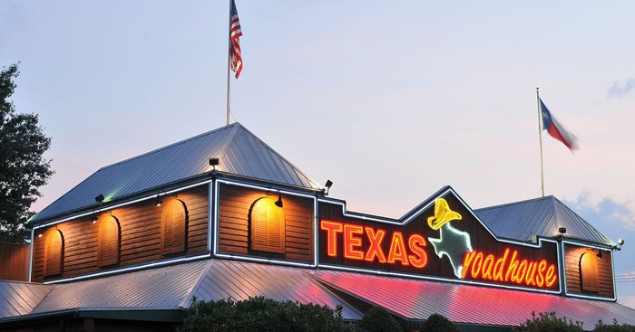 A Texas Roadhouse store with the sign over the door in focus.