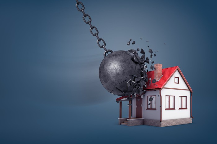 A wrecking ball hits a small house.