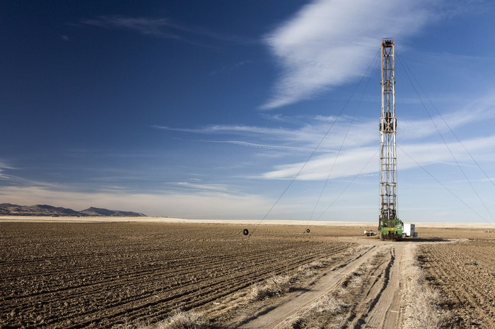 A natural gas fracking rig tower stands alone in a farm field under a blue sky, with mountains in the distance.