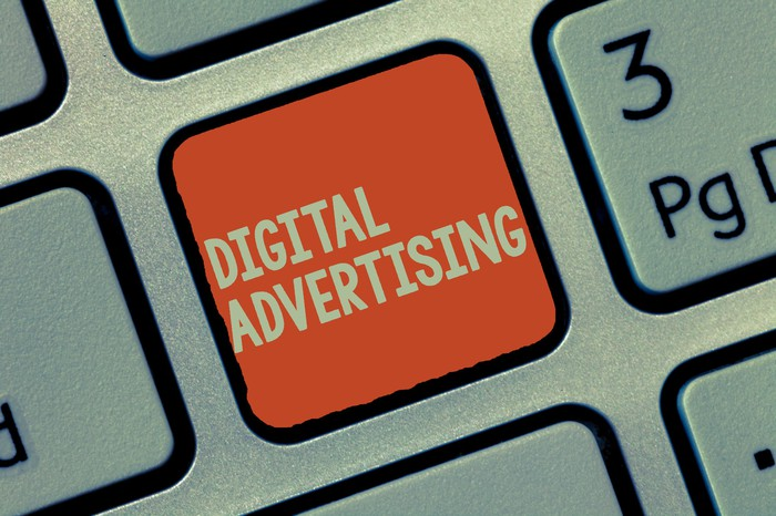 Computer keyboard showing an orange button labeled digital advertising