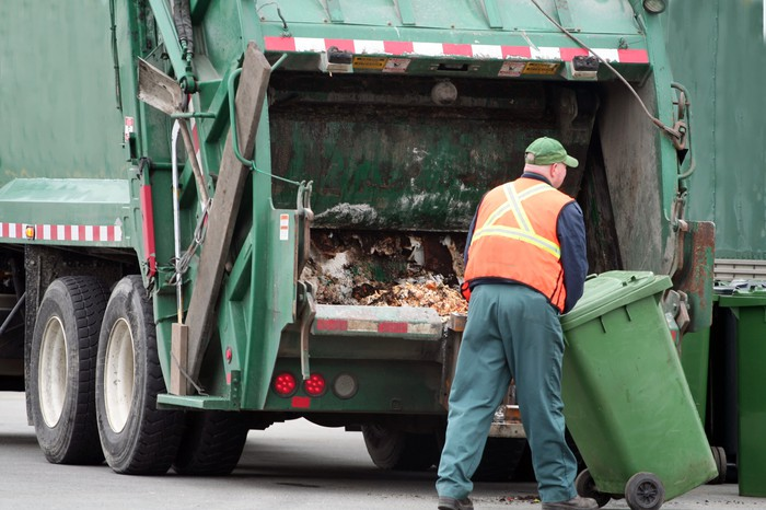 A worker moves a waste bin behind a garbage truck