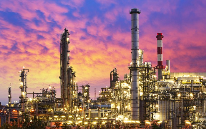 An oil refinery with its exterior lights on at sunset.