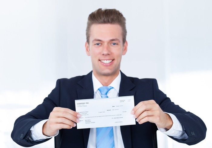 Young man in a suit holds a paycheck and smiles.