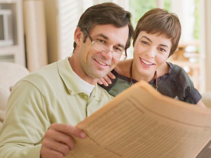 A smiling couple reading the financial section of a newspaper.