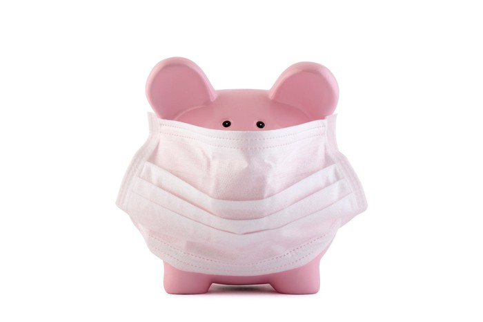 A piggy bank with a surgical mask on its face.