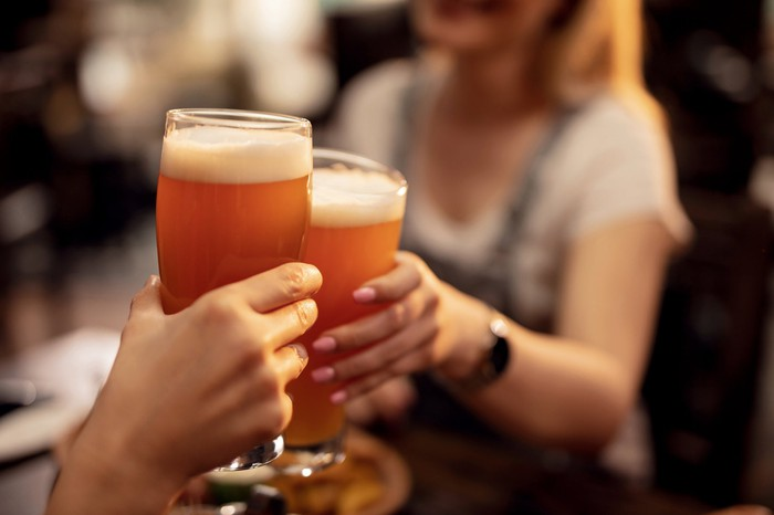 Two women drink beer outside.