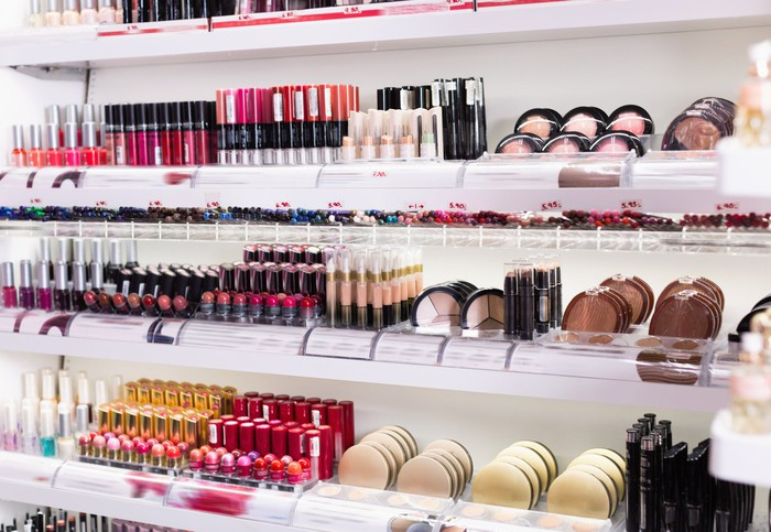Shelves in a cosmetics store are shown, lined with lipsticks and pressed powders.
