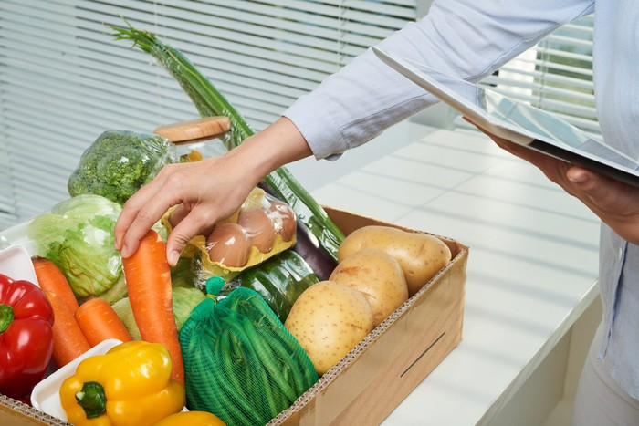 A woman grabbing a carrot from a box of vegetables as she checks her tablet.