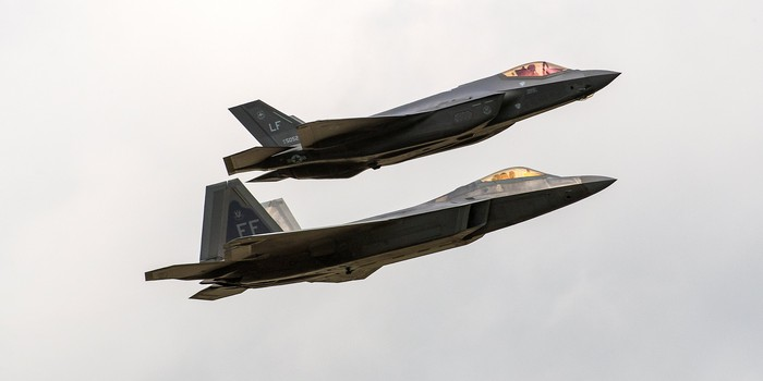 A F-35 and F-22 in position together flying in front of a cloudy sky.