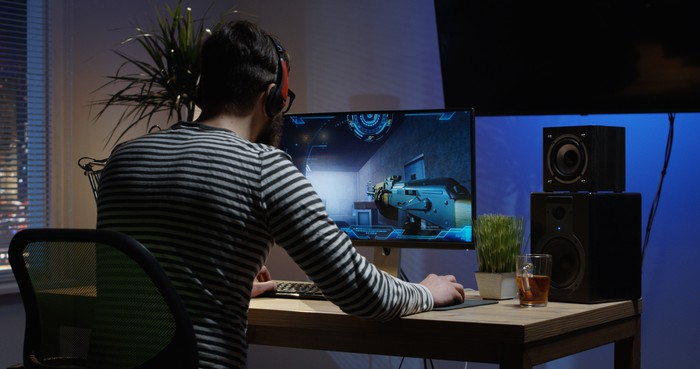 Video game player at desk, playing a game.