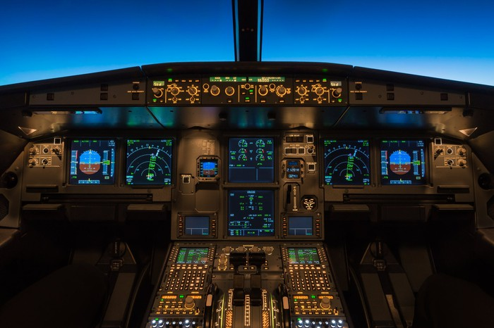 View of sophisticated airplane cockpit, with various avionics and controls, and a dark blue sky out the window.