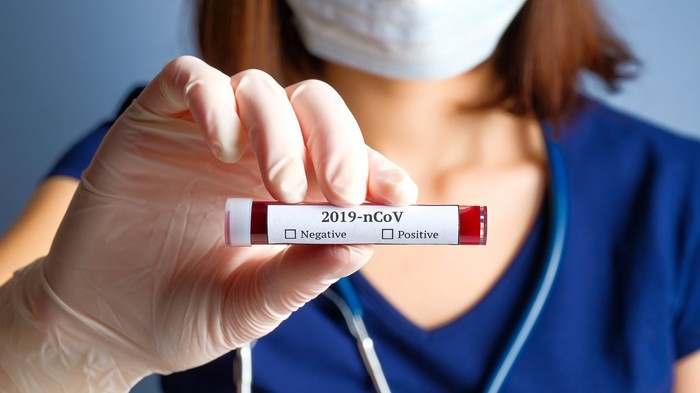 A person in medical attire holding a COVID-19 blood test vial.