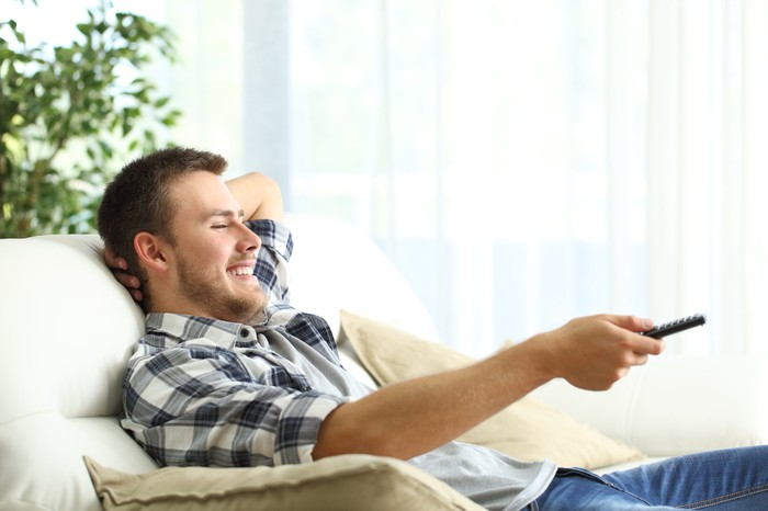 A man on his couch smiling while pointing a remote at his television.