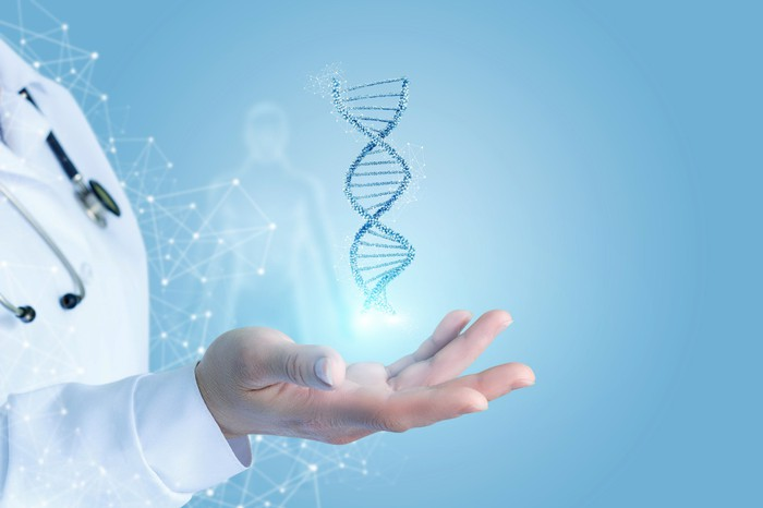 A doctor's outstretched hand with a DNA double helix floating on top.