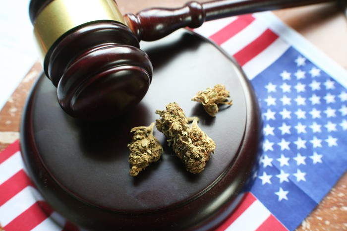 A hammer and gavel on top of an American flag with buds of cannabis next to it.