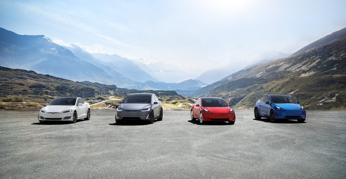 Tesla's different car models lineup up facing camera  in from of mountains.