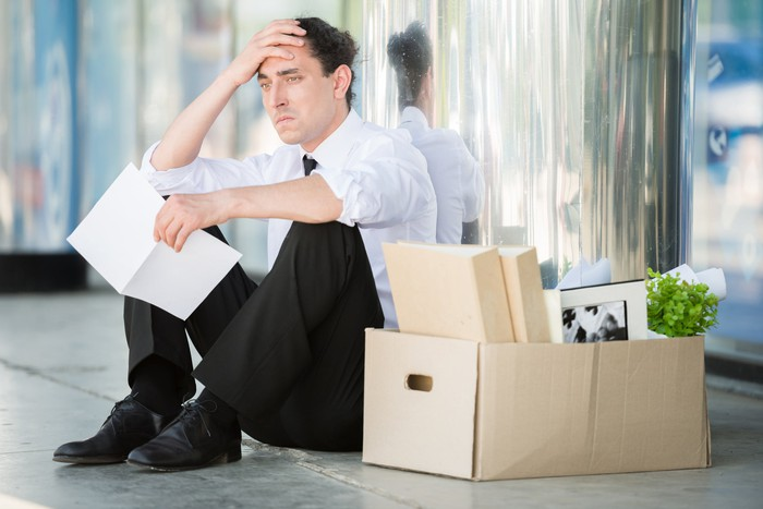 Man sitting next to big box of office supplies, holding his head with one hand and a document with another