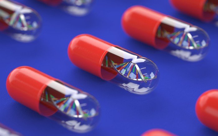 A picture of several pills lined up besides each other, each containing a DNA strand.