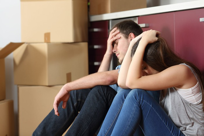 Couple with moving boxes sitting holding their heads