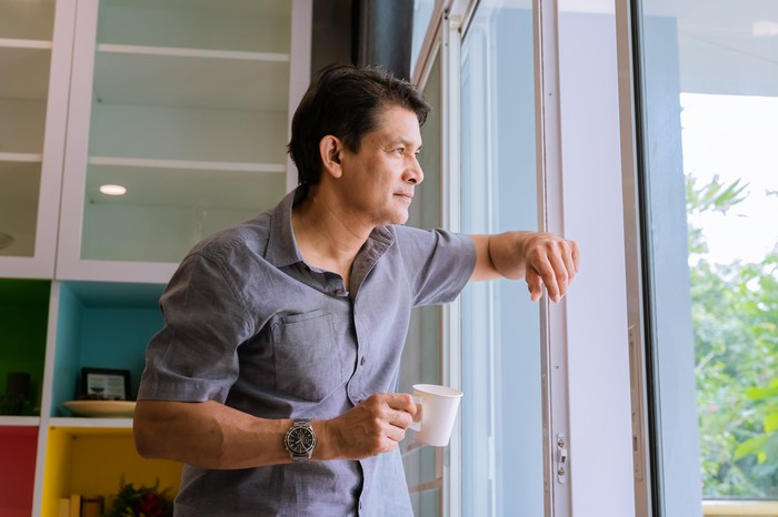 A man looks out the window while drinking coffee.