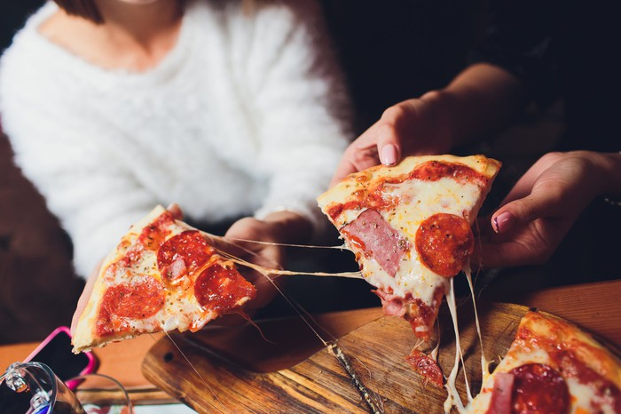 Friends share a delivered pizza.