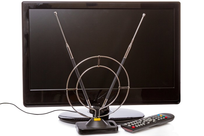 Rabbit ear TV antenna in front of a modern flat screen television