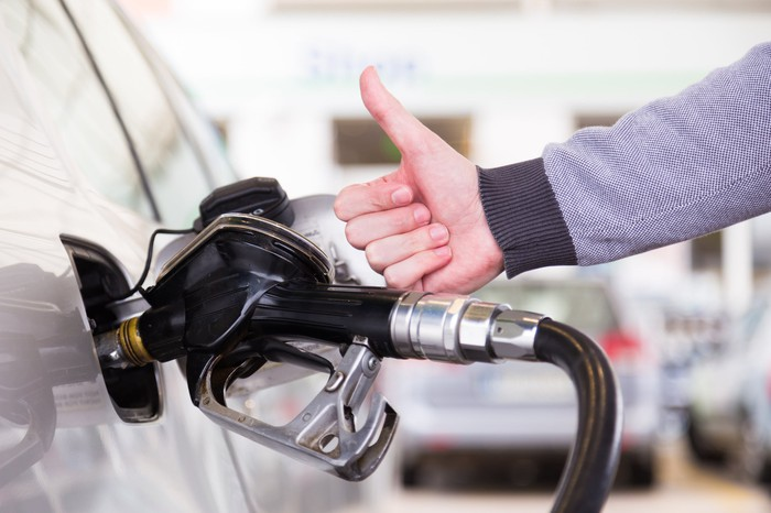 A gas pump refills a car's gas tank while a man's hand gives a thumbs-up.