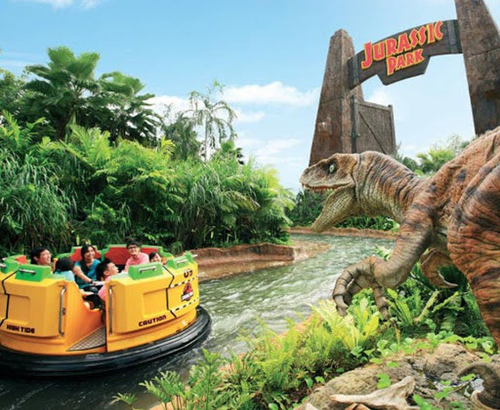 The Jurassic Park ride at Universal Studios. A raft on a river full of visitors with a dinosaur pictured in the foreground.
