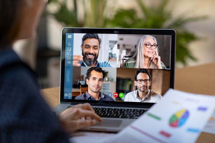 A person on a laptop participating in a video conference with four other people.