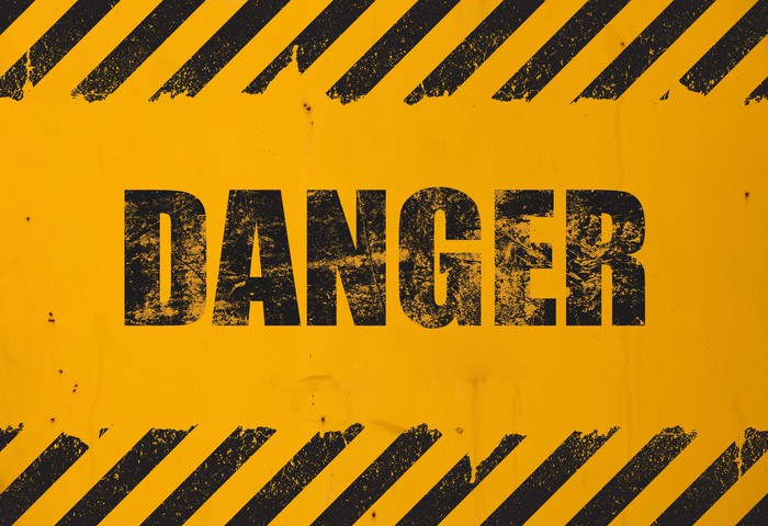 A yellow and black sign that says the word Danger.