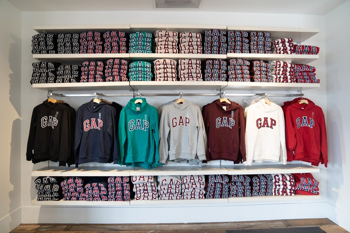 Gap sweatshirts in blue, gray, red, and white are shown hanging on a rack under shelves of folded Gap shirts.