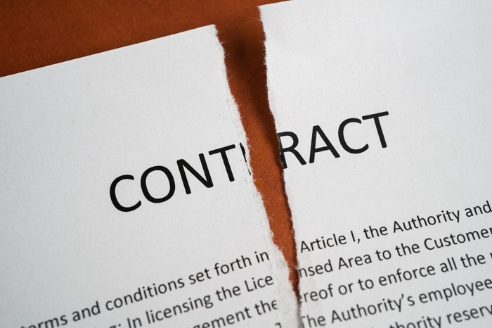 Paper contract being ripped up