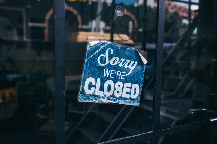 Faded blue sign attached to storefront window reads Sorry we're closed