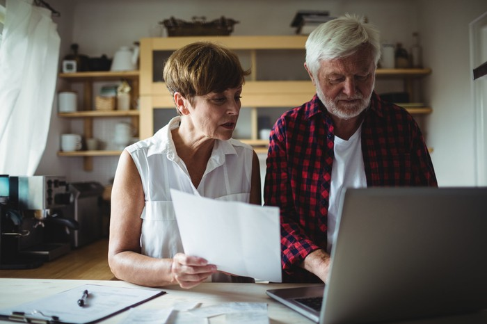Older man types on laptop while older woman next to him holds document