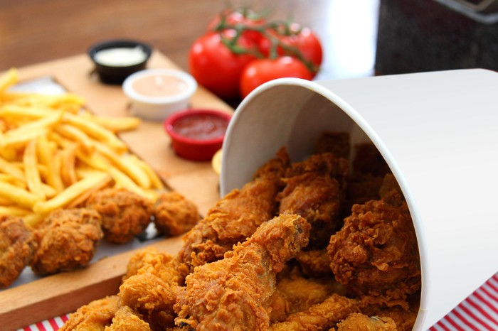 A bucket of fried chicken with fries and condiments in the background.