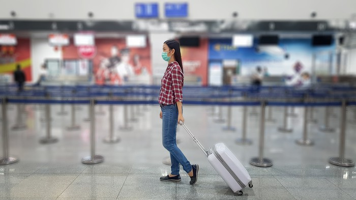 A person walking through an airport, wearing a face mask and toting a suitcase on wheels