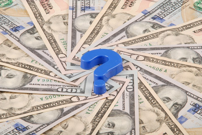 A blue question mark sits at the center of a spiral of fifty and hundred dollar U.S. bills.