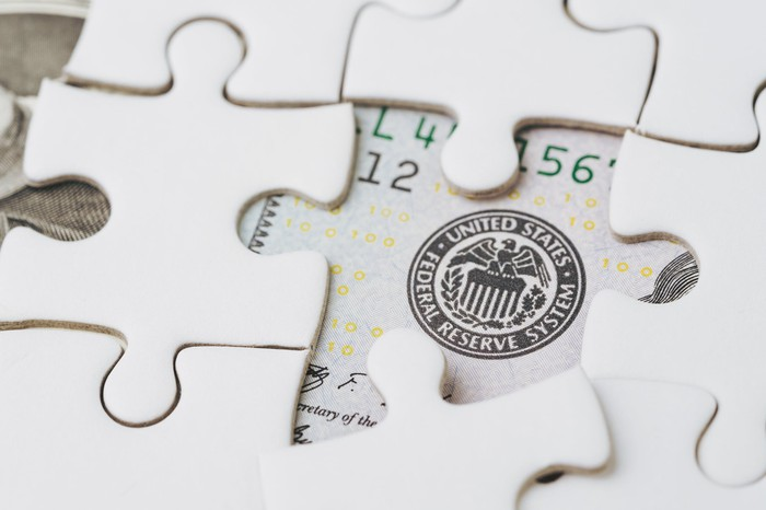 A jigsaw puzzle over a U.S. bill revealing the seal of the Federal Reserve