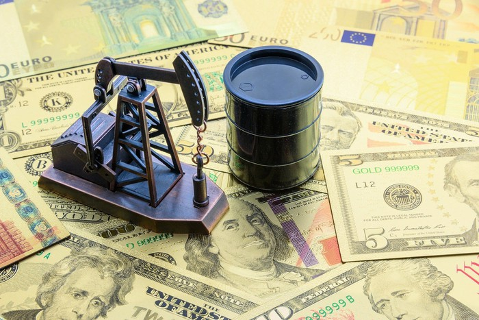 a miniature oil derrick and a barrel of oil atop a pile of paper money