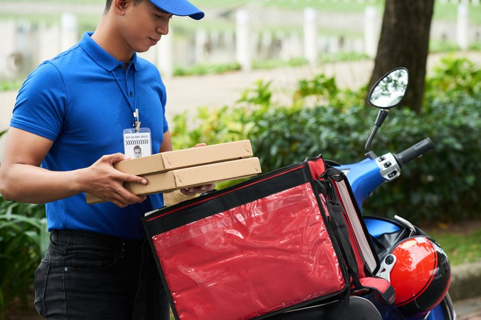 Delivery driver takes boxes of food off his moped.