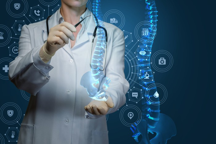A doctor looking at an abstract hi-tech picture of a spine.