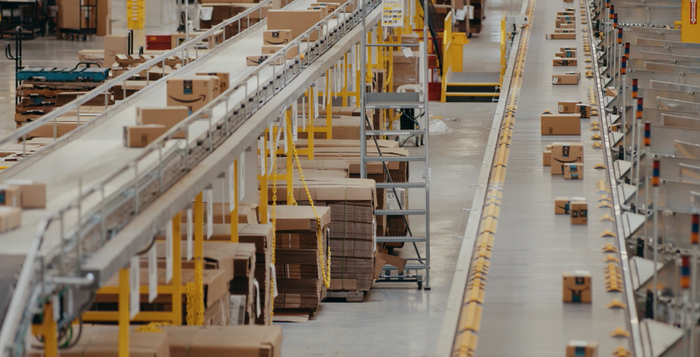 Packages moving on two conveyor belts in an Amazon fulfillment center.