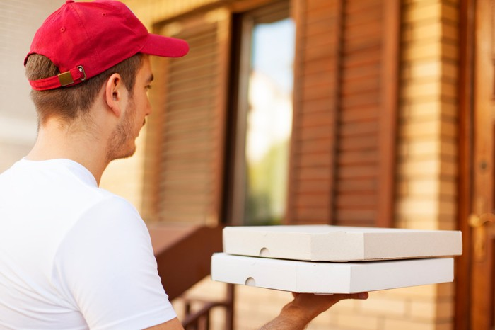 A person delivers two pizzas.