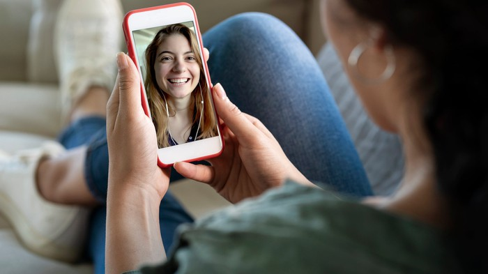 A woman holds a smartphone on which another woman's face is displayed