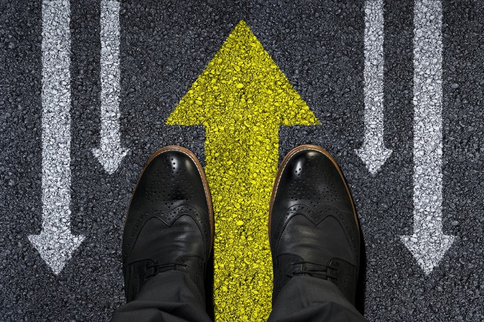 Overhead view of a man's dress shoes straddling a yellow arrow pointing up with white arrows on the sides pointing down