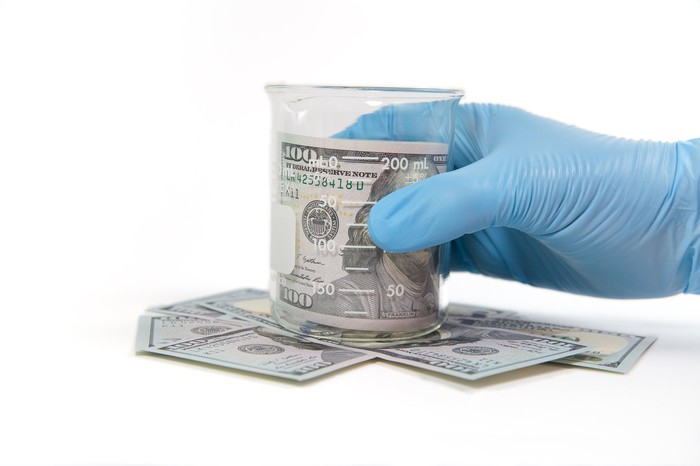Hand wearing a blue glove holding a glass beaker with a hundred dollar bill in it and hundred dollar bills beneath it