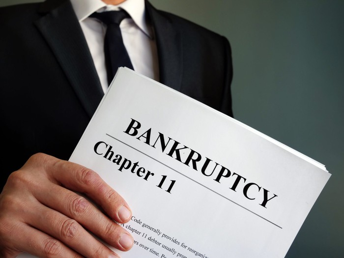 A person in a suit holding papers with Chapter 11 Bankruptcy on them.