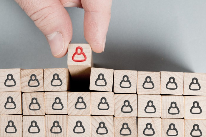 A hand selecting one misfit from a uniform group of wooden blocks
