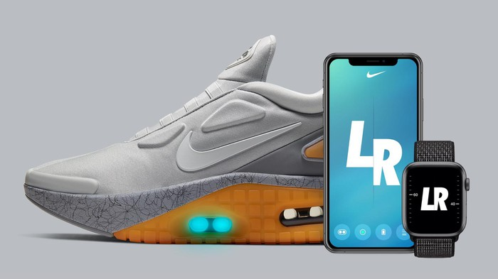 A Nike sneaker next to a smartphone and a smartwatch, each with one of Nike's apps displayed